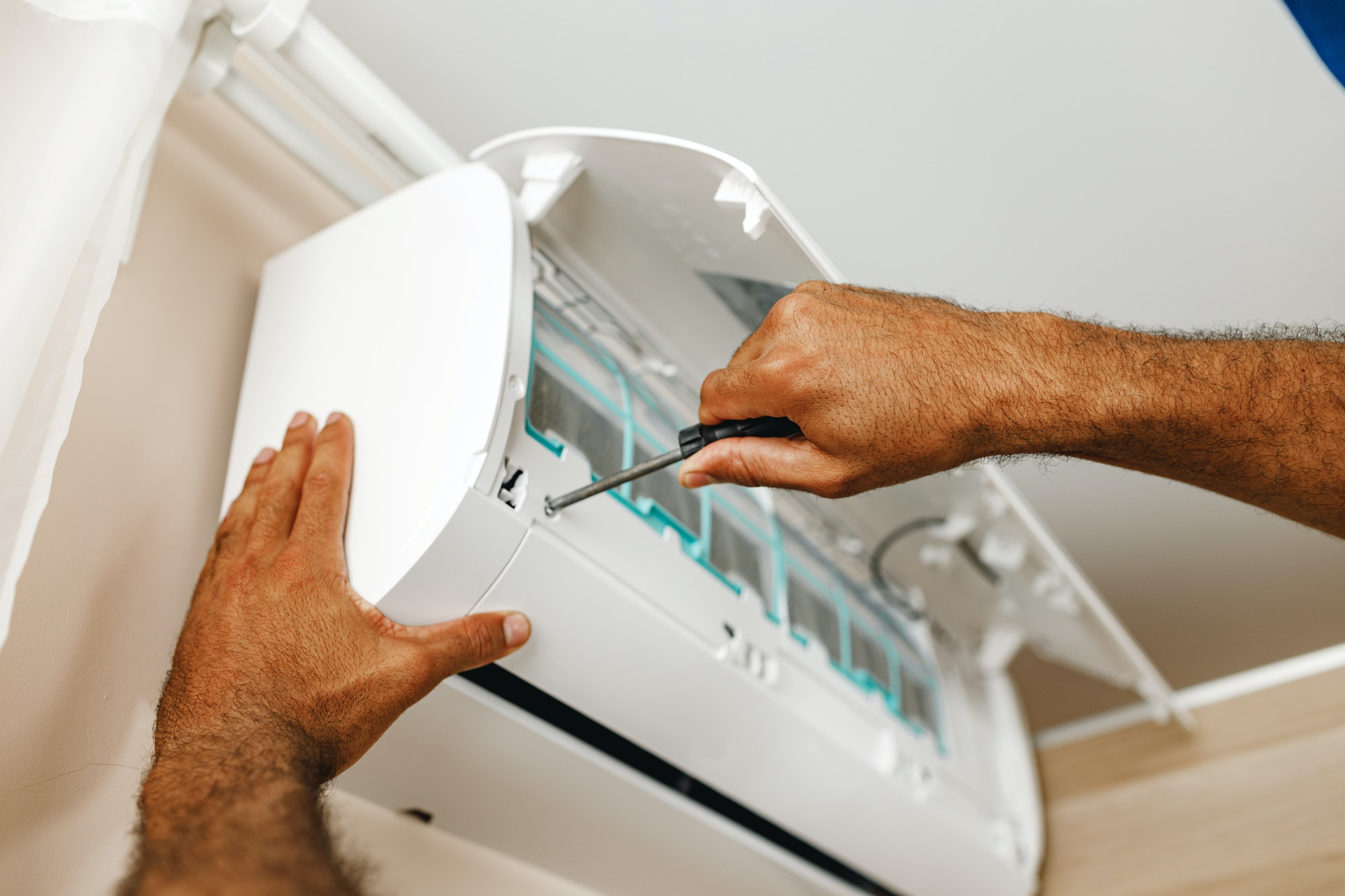 Close up of repairman fixing air conditioner in a room