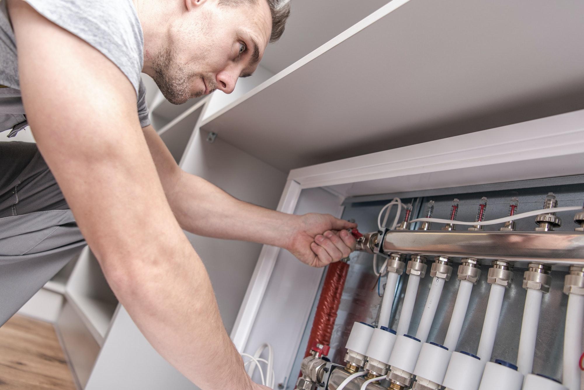Men Adjusting Apartment Heat on the Central System Valves